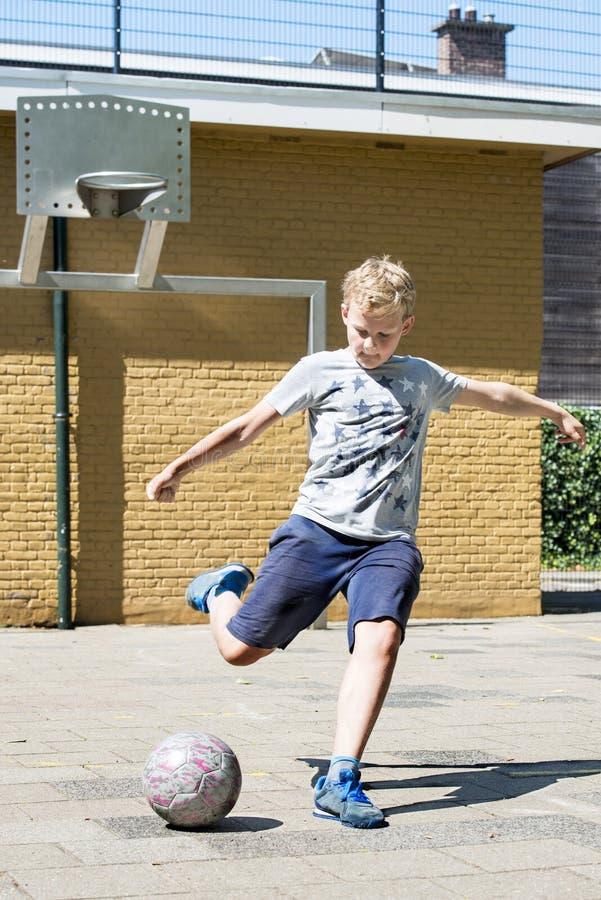 Het schoppen van een bal in een hoogte van het straatvoetbal stock foto