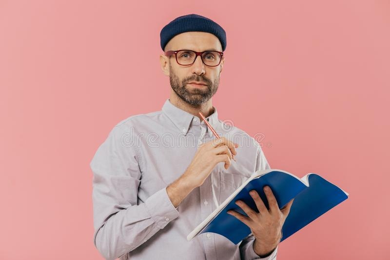 het schot van aantrekkelijk jong mannetje houdt handboek, maakt formeel geklede nota's in organisator, De slimme student treft vo stock afbeelding