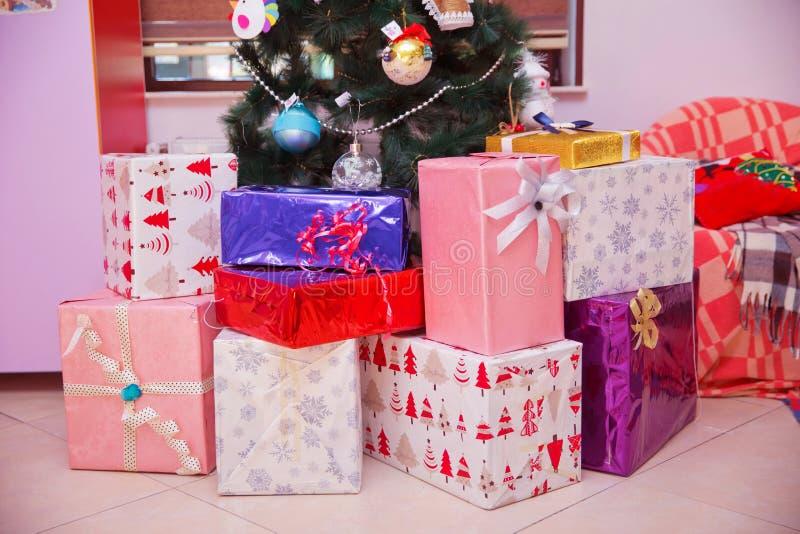 Het schot van een groep dozen met stelt onder een verfraaide Kerstboom voor slinger van het speelgoedsterren van Kerstmis de deco stock foto