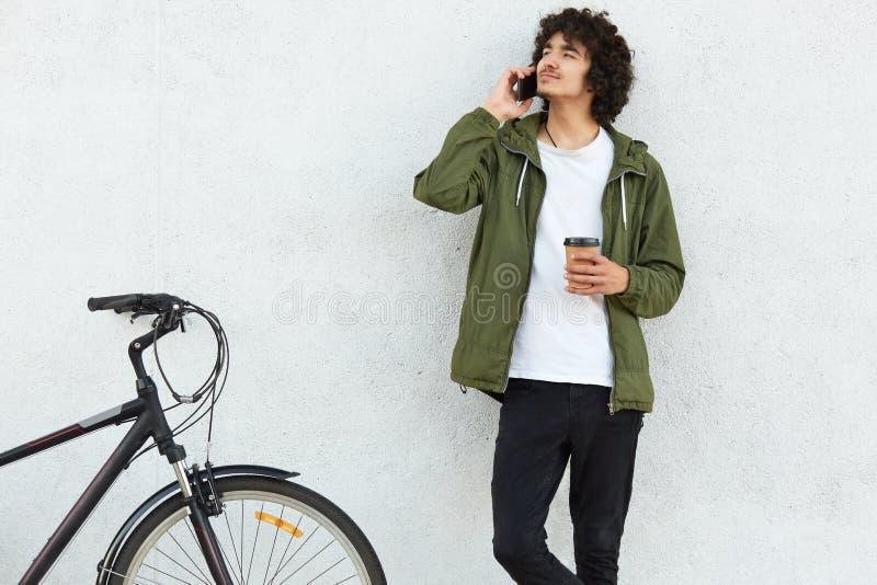Het schot van geconcentreerd mannelijk kereltje spreekt via celtelefoon met meisje, vertelt over zijn fietsreis, houdt meeneemkof stock foto