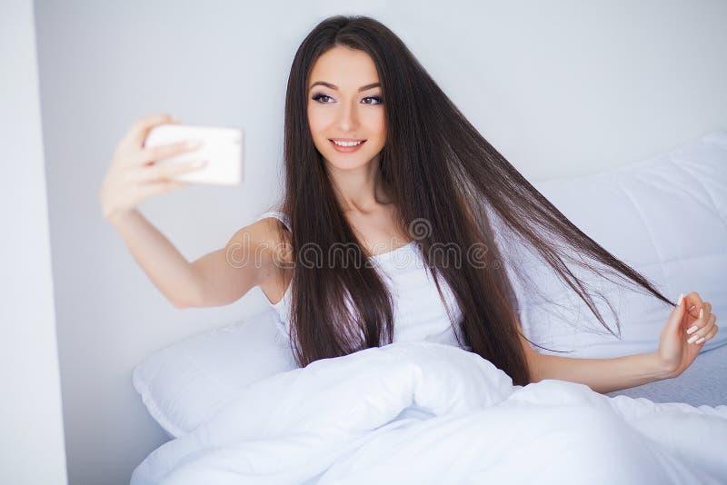 Het schot van Gelukkige leuke vrouw ligt op bed gebruikend mobiele telefoon stock foto