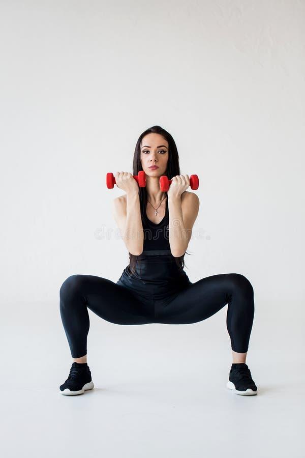Het schot van gemiddelde lengte van de cardioleerprogramma's De atletische trainer doet hurkende tricepuitbreiding met rode domor stock foto