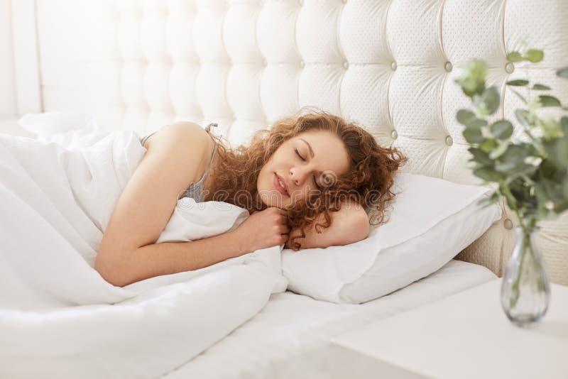 Het schot van krullend mooi meisje heeft prettige dromen en de gezondheidsslaap in wit bed, geniet van goede rust in hotelruimte  royalty-vrije stock fotografie