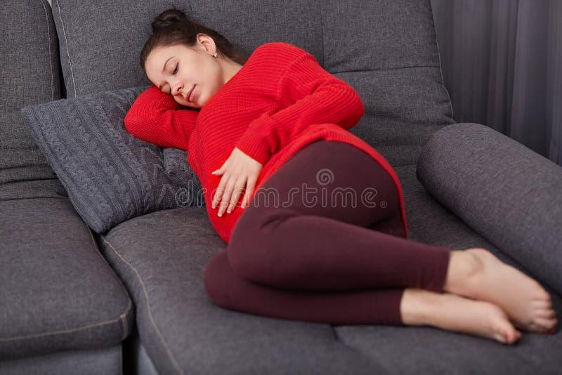 Het schot van rustgevende zwangere vrouw houdt hand op buik, draagt vrijetijdskleding, ligt op comfortabele bank, die dutje, rust stock afbeelding