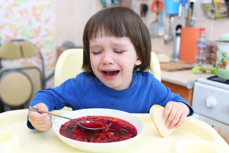 Het schreeuwende kind wil geen rode soep eten royalty-vrije stock afbeeldingen