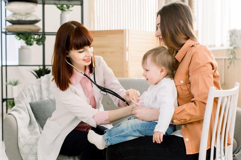 Het schreeuwende zieke meisje van de jong geitjebaby op moeder dient het ziekenhuis of thuis, en vrouwelijke GP arts in die onder royalty-vrije stock fotografie