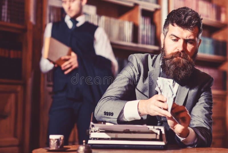 Het schrijven en prijzenconcept De mens in ouderwets kostuum houdt geld stock foto