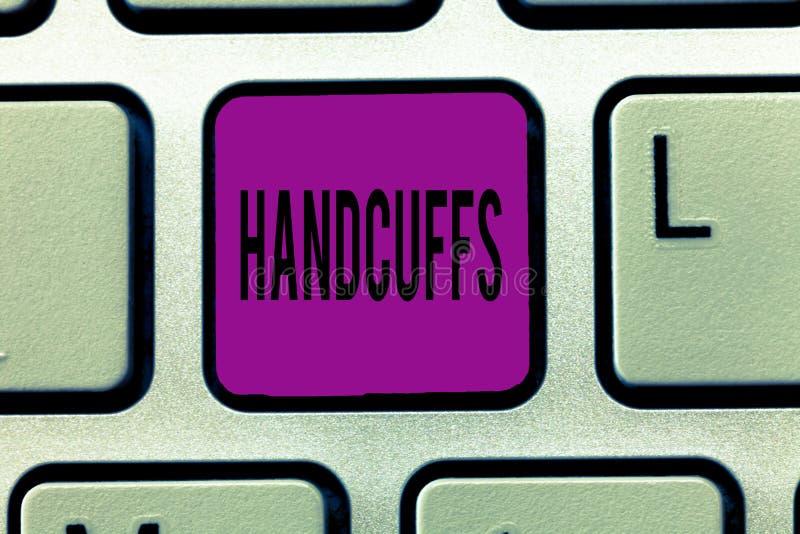 Het schrijven nota die Handcuffs tonen Bedrijfsfoto demonstratiepaar afsluitbare verbonden metaalringen voor het beveiligen van e royalty-vrije stock afbeelding
