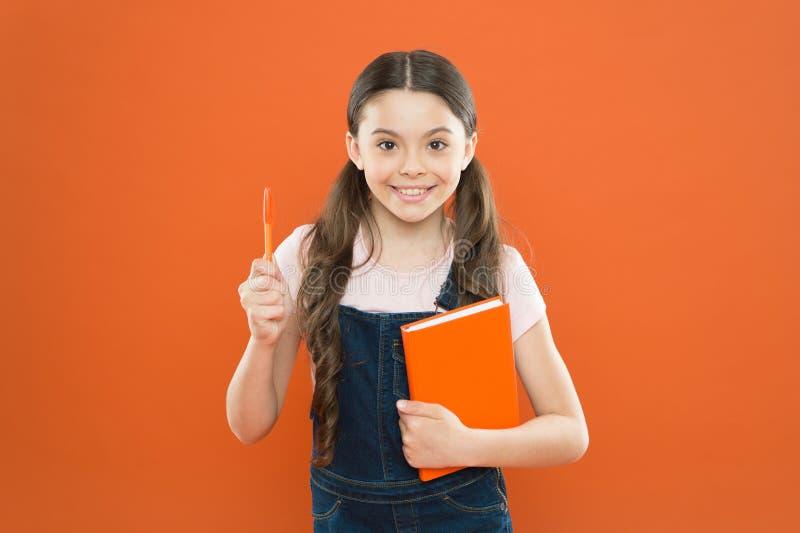 Het schrijven nota's jong geitjeagenda schoolmeisje gelezen boek op oranje achtergrond Gelukkig meisje met notitieboekje poëzie e stock fotografie