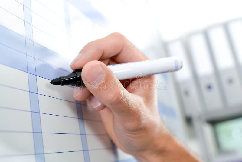 Het schrijven op grafiek met markeerstift stock foto's