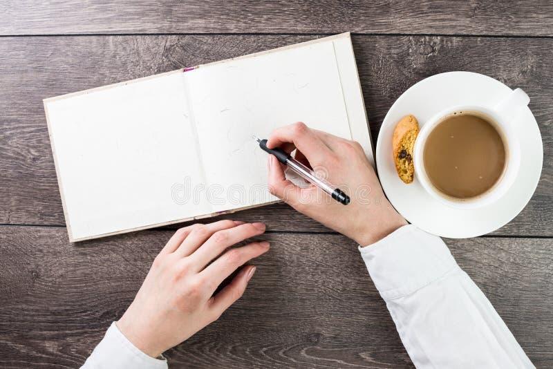 Het schrijven op leeg (leeg) boek (nota, agenda) uitgespreid model stock foto's