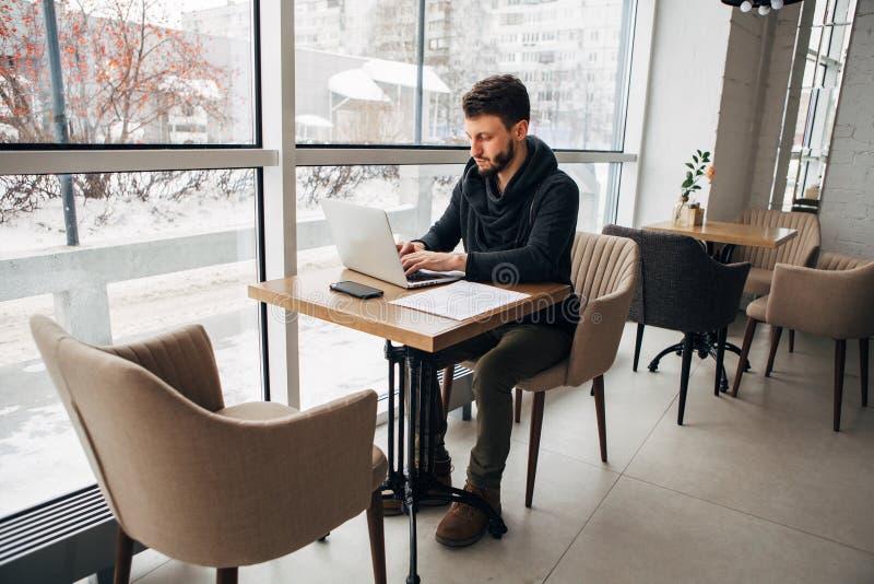 Het schrijven post van koffie Een close-updeel van de jonge gebaarde mens die zijn laptop met behulp van terwijl het zitten bij k royalty-vrije stock afbeeldingen