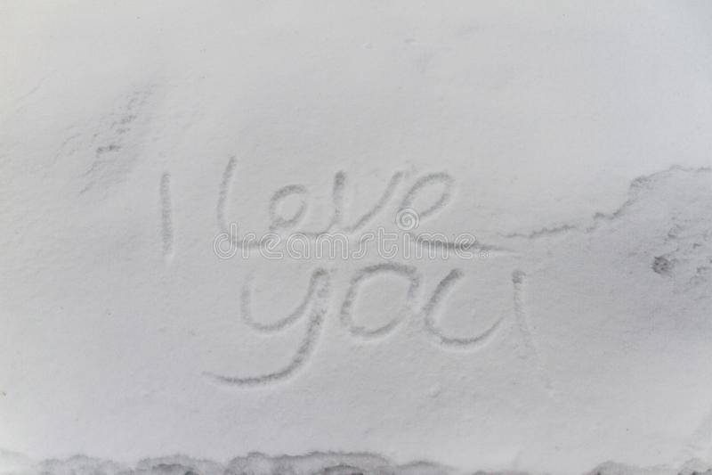 Het schrijven tekstliefde U op de sneeuw stock foto