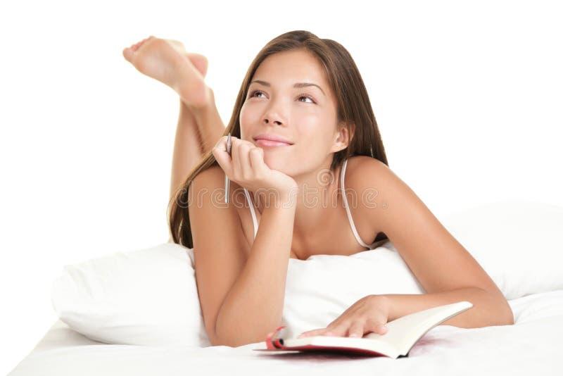 Het schrijven van de vrouw agenda in bed royalty-vrije stock foto