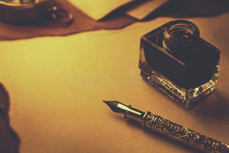 Het schrijven van document met ganzepen en inkt op oud perkamentdocument stock fotografie