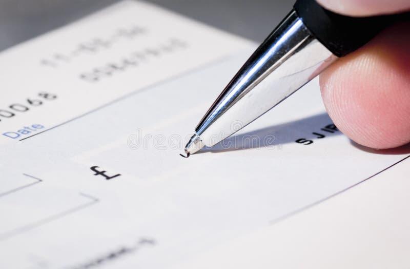 Het schrijven van een cheque stock foto