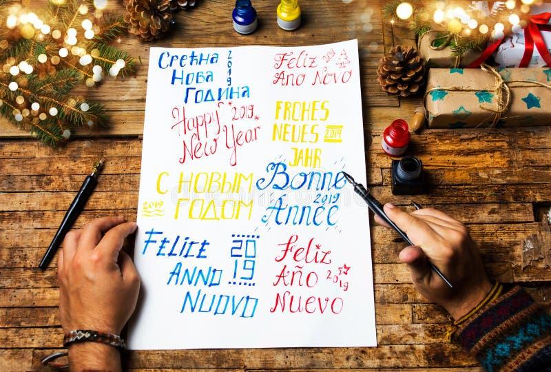 Het schrijven van een Gelukkige nieuwe jaarkaart in diverse talen stock foto