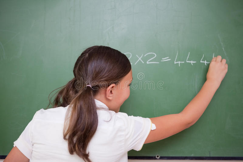 Het schrijven van het schoolmeisje aantallen stock fotografie