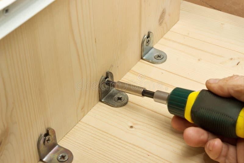 Het schroeven van een schroef bij productie van meubilair stock foto