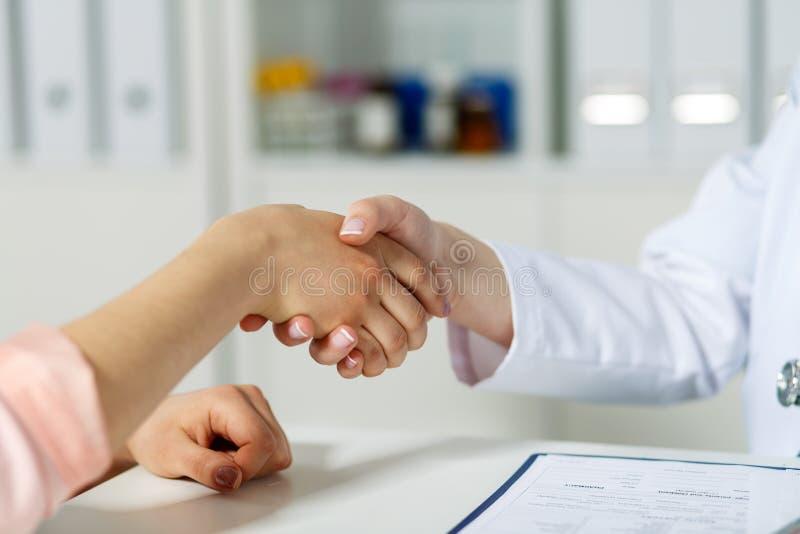 Het schudden van de arts hand met patiënt stock afbeeldingen
