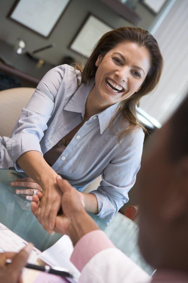 Het schudden van de vrouw de hand van de arts bij kliniek IVF