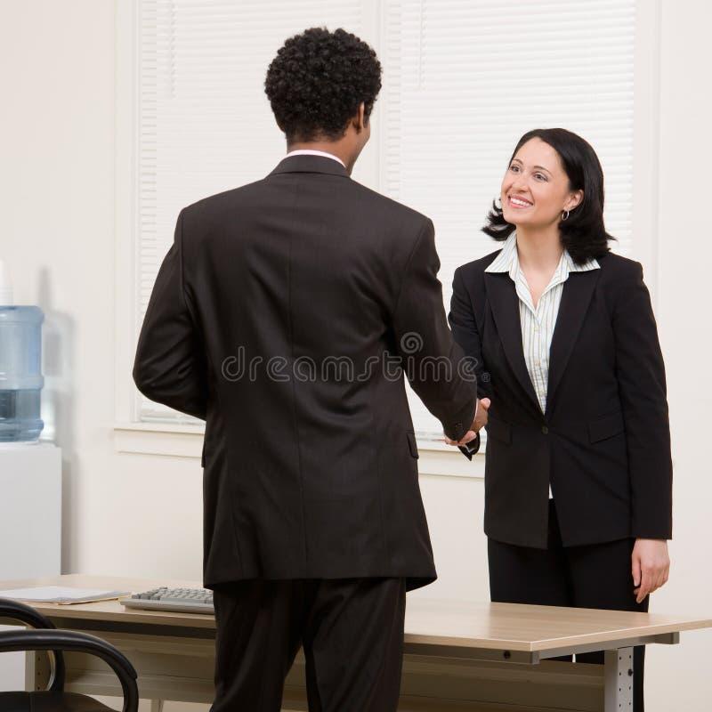 Het schudden van de vrouw handen met medewerker bij bureau royalty-vrije stock foto