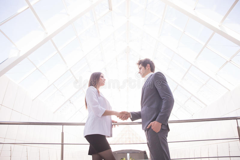 Het Schudden van de zakenman en van de Onderneemster dient Bureau in Bedrijfs concept stock foto's