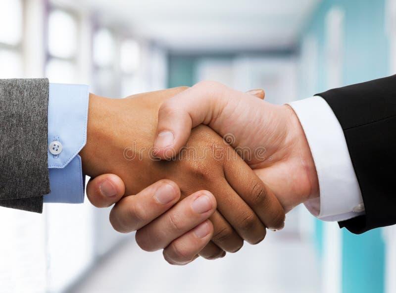 Het schudden van de zakenman en van de onderneemster handen stock afbeelding