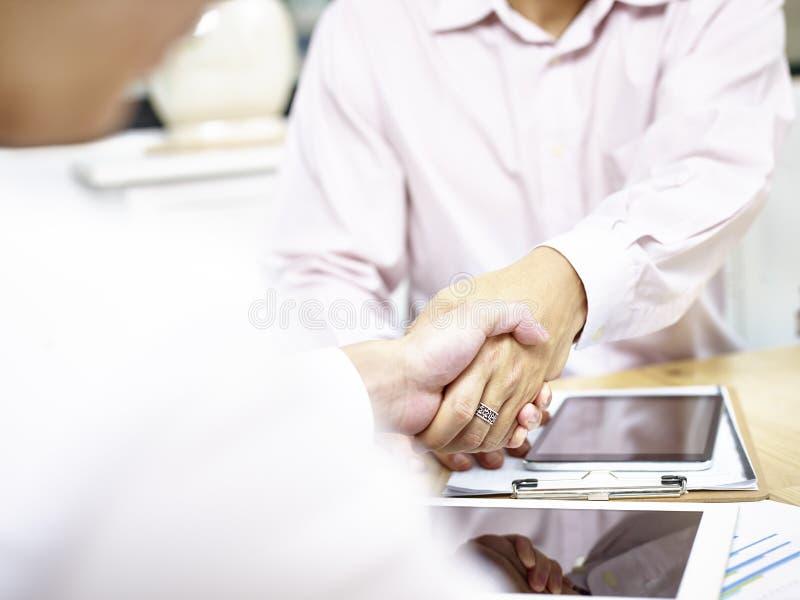 Het schudden van zakenlieden dient bureau in stock afbeelding