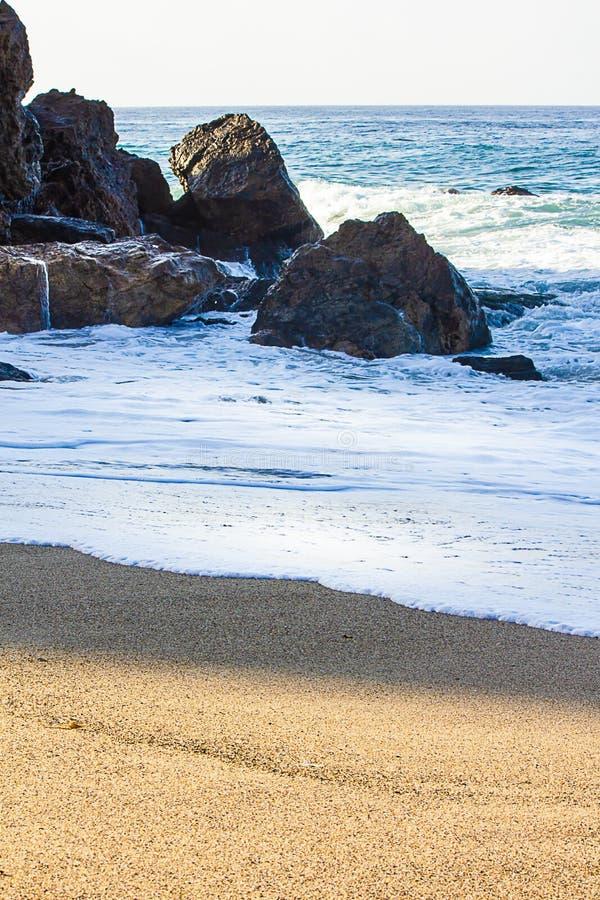 Het schuim die zich over het zandige strand met terugslag door rotsen terug naar oceaan bewegen zwelt royalty-vrije stock afbeeldingen