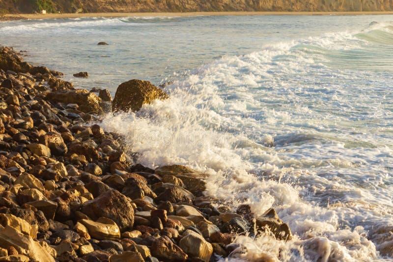 Het schuimen de was van de pastelkleurgolf over baai met verre golfterugslag, die op rotsachtige oever breken stock afbeelding