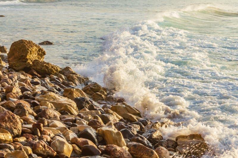 Het schuimen de was van de pastelkleurgolf over baai met verre golfterugslag, die op rotsachtige oever breken stock foto