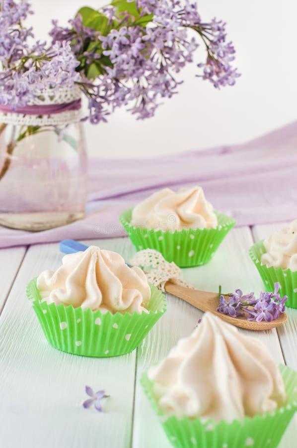 Het schuimgebakje koekt dichtbij lilac bloemen royalty-vrije stock fotografie