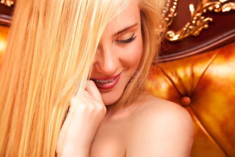 Het schuwe jonge blonde glimlachen royalty-vrije stock fotografie