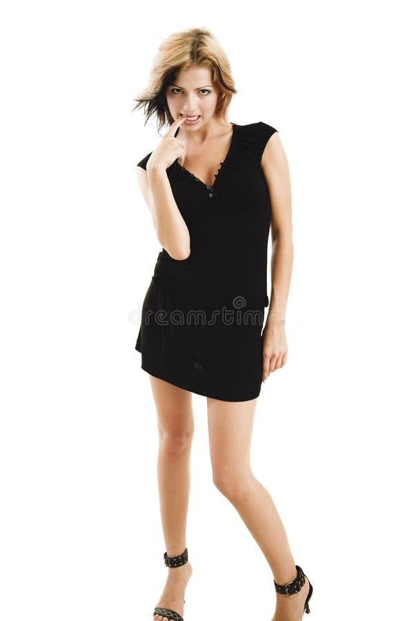 Het schuwe jonge model stellen in een leuke zwarte kleding stock fotografie