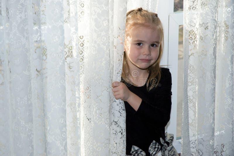 Het schuwe meisje verbergen achter gordijn stock foto