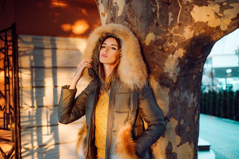 Het seizoen van de herfst Weg in dalingsbos Schitterende mooie vrouw op bont de tribune stedelijke achtergrond van het laagjasje  royalty-vrije stock foto