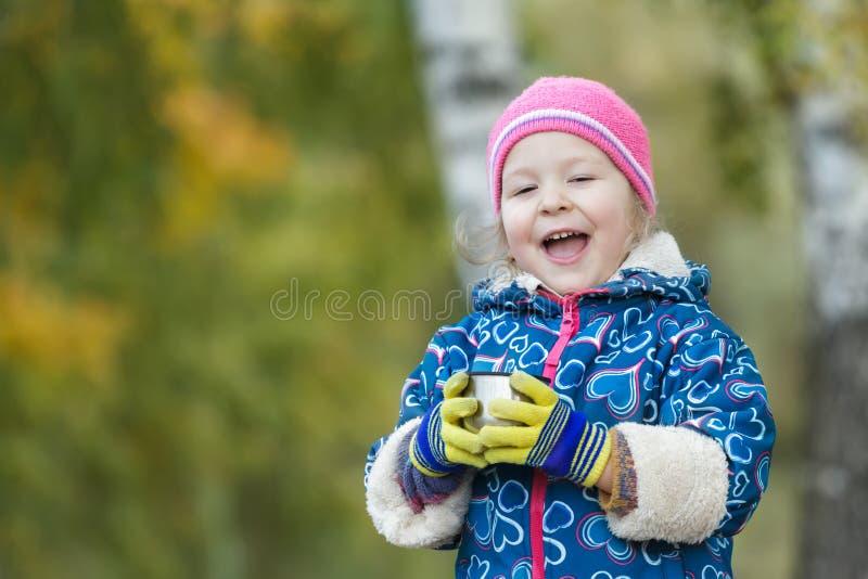Het seizoengebonden openluchthoofd en het schoudersportret van het staalthermosfles van de meisjeholding vormen in handen tot een royalty-vrije stock foto's