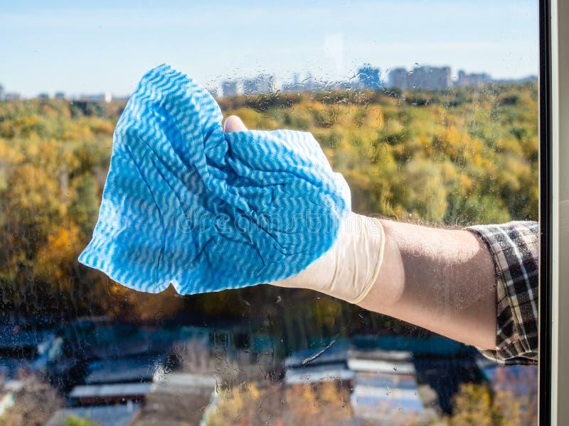 het seizoengebonden schoonmakende glas van het huisvenster door blauw vod royalty-vrije stock foto's