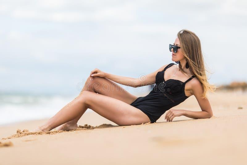 Het seksuele jonge meisje neemt sunbath het liggen op zand op het strand die modieuze swimwear dragen Het genieten van de zomer v royalty-vrije stock foto's