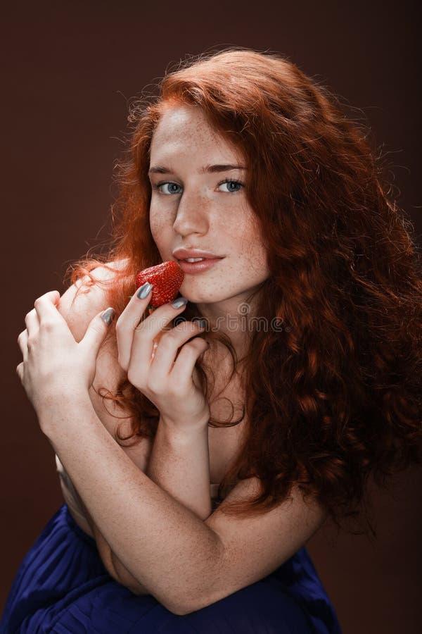 Het sensuele aantrekkelijke roodharigevrouw stellen met aardbei royalty-vrije stock afbeeldingen