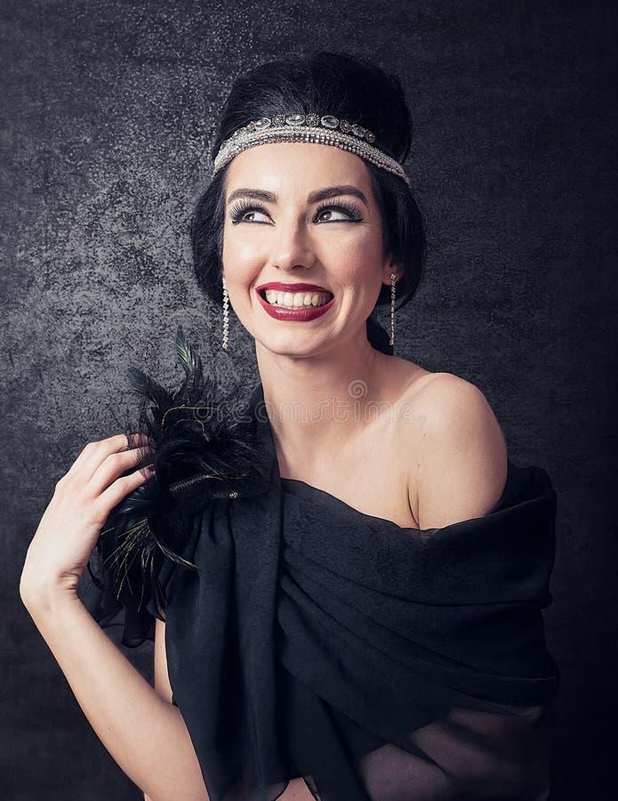 Het sensuele brunette met retro jaren '20 kijkt glimlachend op zwarte glowi royalty-vrije stock afbeeldingen