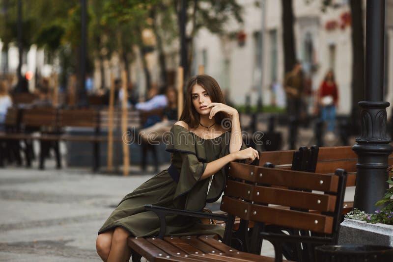Het sensuele en modieuze donkerbruine modelmeisje in modieuze kleding met naakte schouders zit op een bank en het stellen in open royalty-vrije stock afbeeldingen