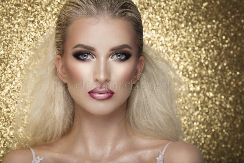 Het sensuele mooie blondevrouw stellen in witte kleding over gouden B stock afbeeldingen