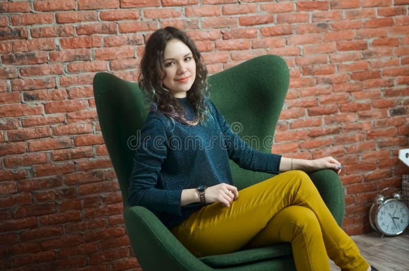 Het sensuele mooie meisje stellen in groene sweater stock afbeelding