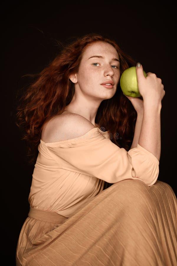 Het sensuele roodharigevrouw stellen met groene appel stock fotografie