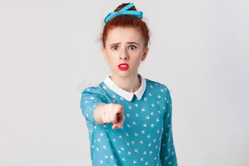 Het seriosly roodharigemeisje, die blauwe kleding dragen, openend geschokt monden die wijd, bekijkt, richtend vinger camera hebbe stock afbeeldingen