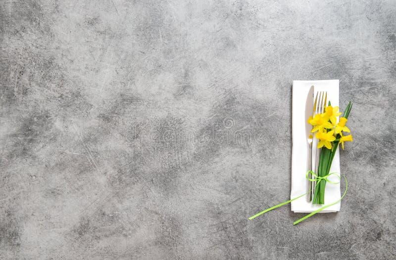 Het servet van het vorkmes op de lentebloemen van de lijstplaat stock afbeelding
