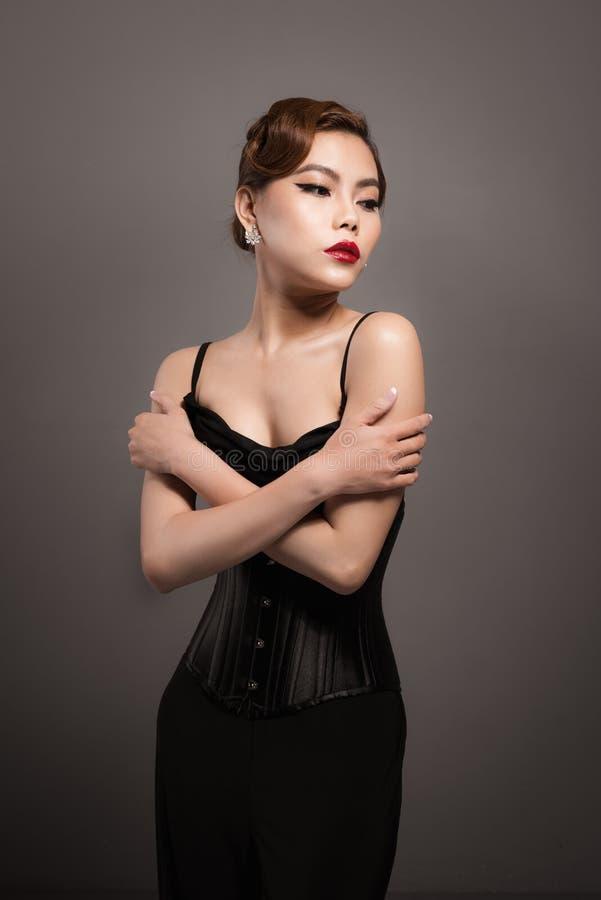 Het sexy aantrekkelijke Aziatische vrouw stellen in modieuze zwarte kleding ov stock foto