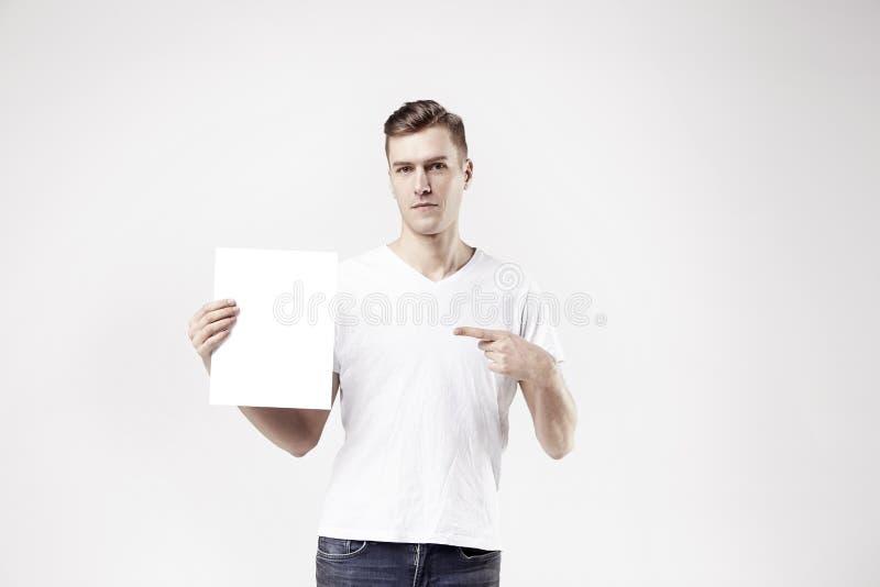 Het sexy aantrekkelijke mensenmodel toont wit leeg ruimtedocument A4 voor advertentie stock afbeelding